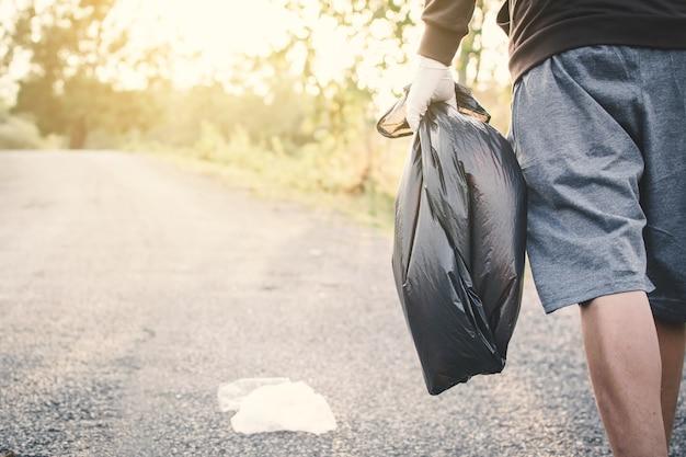 Sac poubelle humain ramasser du plastique sur le parc