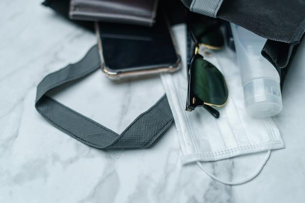 Sac à provisions avec articles indispensables pour téléphone intelligent, masque protecteur, lunettes et gel désinfectant, virus corona ou protection covid-19.
