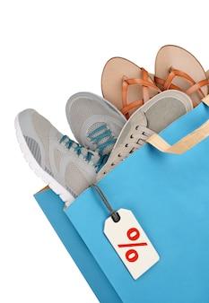 Sac à provisions avec des chaussures isolé sur fond blanc