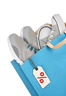 Sac à provisions avec des chaussures de sport isolé sur fond blanc