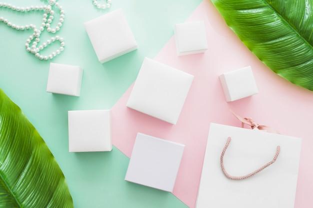 Sac à provisions, collier de perles et différents types de boîtes blanches sur fond de papier pastel