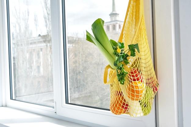 Sac à provisions à cordes jaune avec des légumes et des fruits accrochés à la poignée de la fenêtre de la cuisine