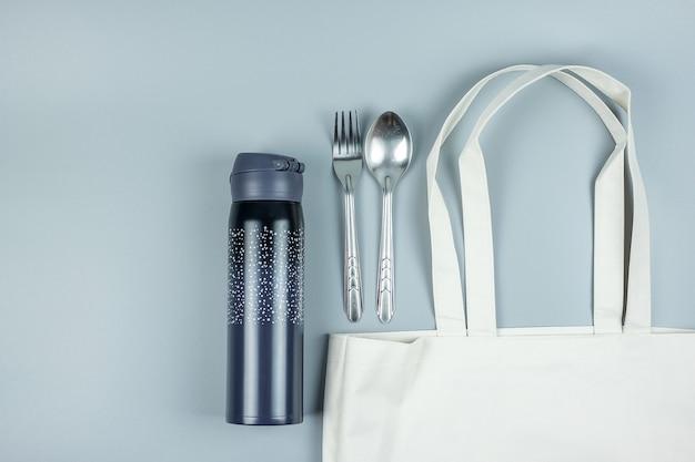 Sac à provisions eco, cuillère et fourchette en acier inoxydable, bouteille d'eau. protection de l'environnement, zéro déchet, réutilisable, ne dites pas de plastique, concept de la journée mondiale de l'environnement et du jour de la terre