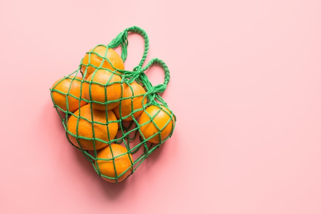 Sac à provisions avec orange sur rose. concept zéro déchet. espace pour le texte.