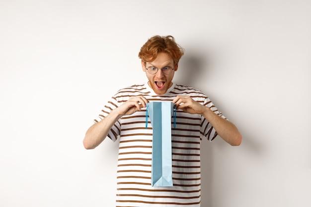 Sac à provisions ouvert petit ami surpris avec cadeau de saint valentin, regardant à l'intérieur avec un visage étonné, debout sur fond blanc.