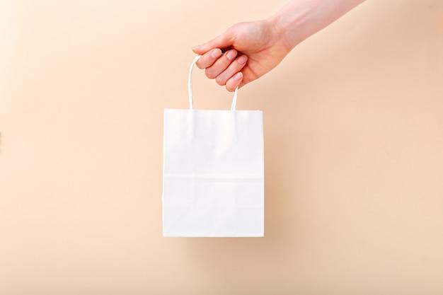 Sac à provisions en papier blanc à la main féminine sur fond de couleur beige clair.