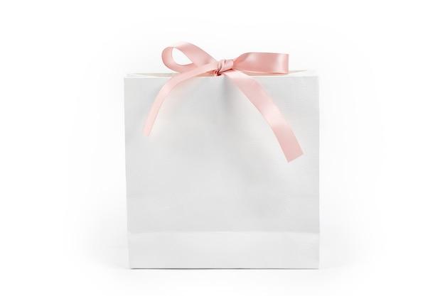 Sac à provisions en papier blanc avec noeud rose sur fond blanc. concept présent, cadeau, shopping et vente.