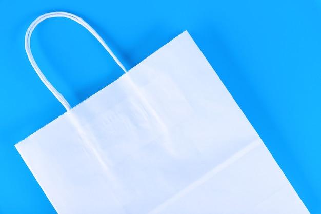 Sac à provisions en papier blanc avec poignées sur fond bleu.