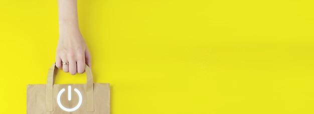 Sac à provisions en papier brun recyclé à la main avec l'icône du bouton hologramme sur fond jaune, mise à plat. démarrez le concept d'entreprise. concept de mise sous tension.