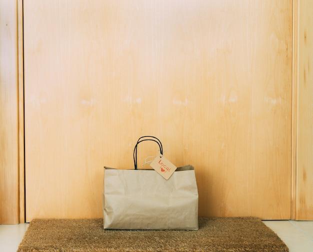 Sac à provisions en papier avec étiquette en carton sur la porte d'entrée de la maison. concept de shopping.
