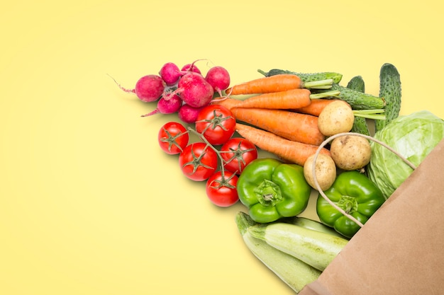 Sac à provisions en papier et légumes biologiques frais sur fond jaune clair. concept d'achat de légumes de la ferme, en prenant soin de la santé, du végétarisme. style champêtre, foire agricole. mise à plat, vue de dessus