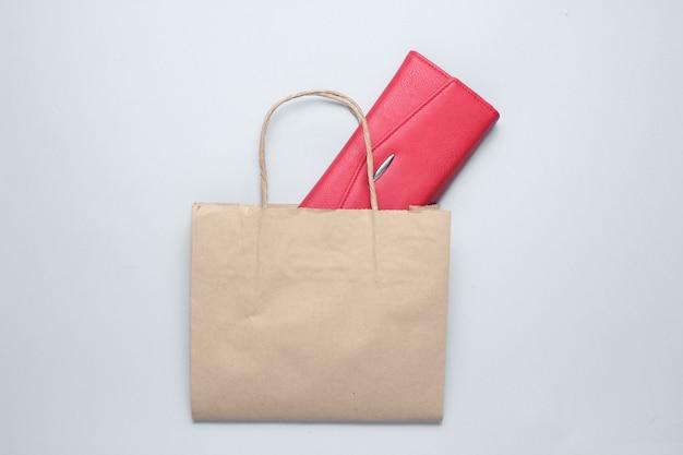Sac à provisions en papier, portefeuille en cuir rouge sur table grise. vue de dessus