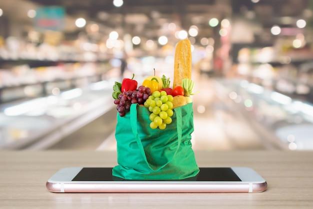 Sac à provisions vert sur téléphone mobile avec supermarché