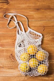 Sac recyclable avec des oranges sur fond de bois