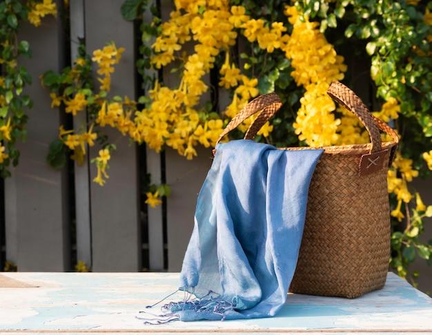 Sac en rotin fait à la main, écharpe bleue sur une table en bois bleu rétro avec de belles fleurs jaunes