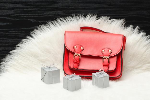 Sac rouge et mini boîte cadeau sur fourrure blanche.