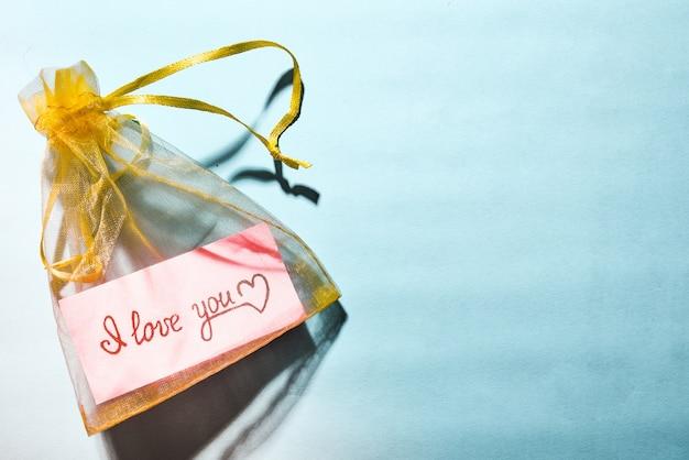 Sac en satin jaune avec un morceau de papier rose et l'inscription i love you sur fond bleu