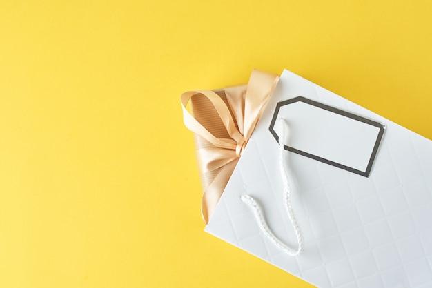 Sac shopping blanc avec boîte-cadeau sur bleu, vue de dessus