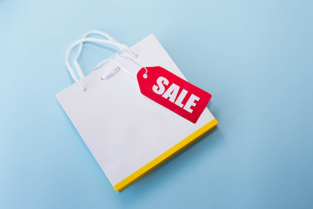 Sac shopping blanc avec une étiquette rouge en vente sur le bleu. espace de copie