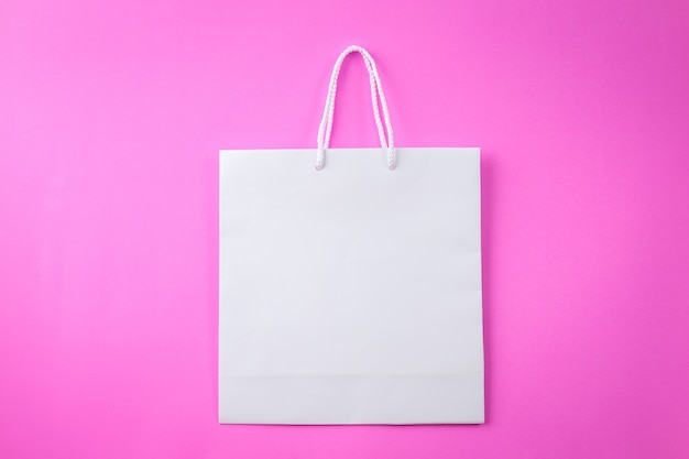 Sac shopping blanc, fond rose et espace de copie pour le texte brut ou le produit