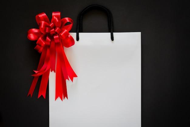 Sac shopping blanc avec noeud rouge et ruban sur fond noir