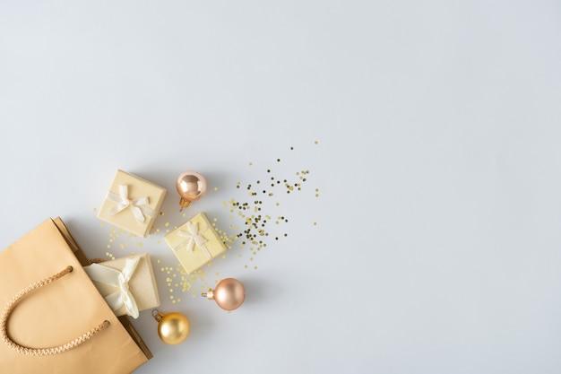 Sac shopping cadeau avec des cadeaux et décoration de boule de noël et paillettes solden. concept de vente de vacances. mise à plat.