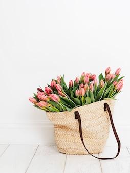 Sac shopping écologique composé de tulipes devant un fond de mur blanc