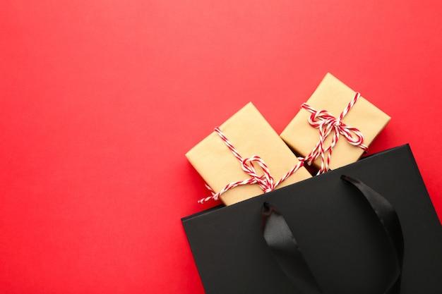 Sac shopping noir avec des cadeaux sur un rouge.