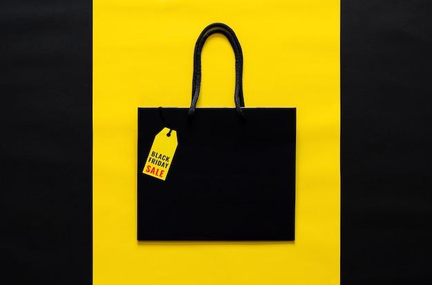 Sac shopping noir avec étiquette de prix jaune sur fond jaune et noir pour le concept de vente shopping black friday.