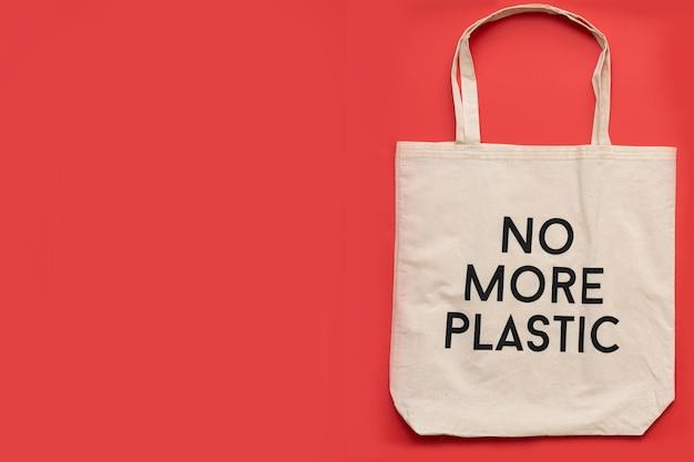Sac shopping réutilisable plus de plastique sur fond rouge. shopper en coton sur fond gris, place pour le textevue de dessus