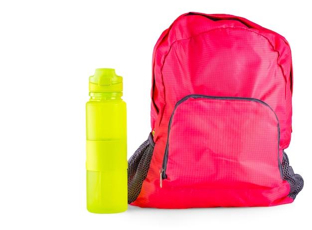 Le sac de sport pour femmes rouge avec une bouteille de sport pour une eau isolé sur blanc