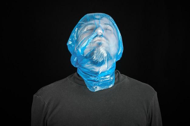 Sac de suicide sur la tête de l'homme. sac de sortie pour suicide. concept d'auto-asphyxie. sac poubelle sur la tête. essoufflement, manque d'air. fond noir.