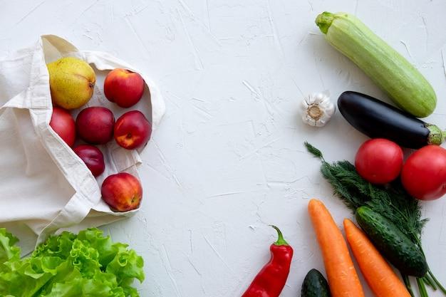 Sac en textile rempli de fruits et légumes, vue de dessus sur blanc.
