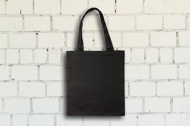 Sac en tissu noir contre mur de briques vintage