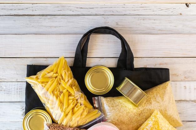 Sac en tissu zéro déchet avec approvisionnement alimentaire quarantaine crise alimentaire isolé sur un fond blanc en bois. riz, pâtes alimentaires, conserves, plastiques de maïs, papier hygiénique. livraison de nourriture, concept de don.
