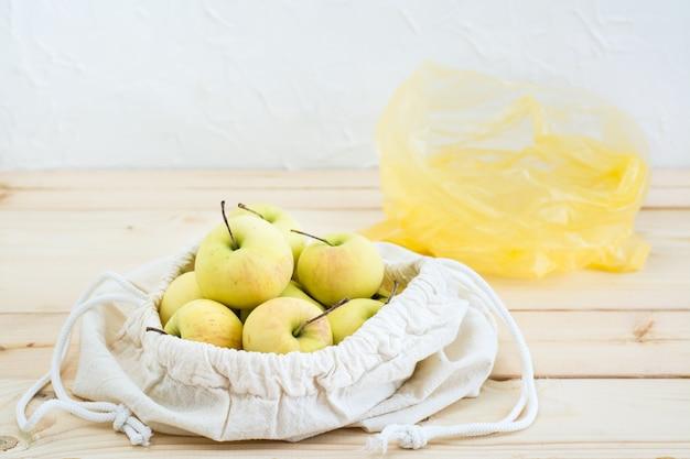 Sac en toile avec des liens avec des pommes et un sac en plastique sur un fond en bois naturel