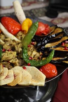 Sac traditionnel du caucase avec pommes de terre frites, tranches d'aubergines, tomates, poivrons et ragoût de boeuf