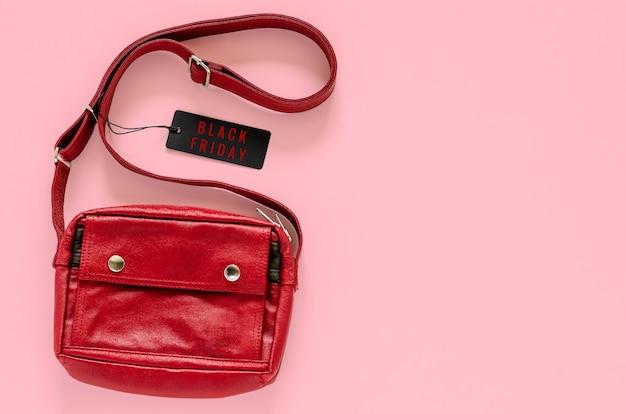 Sac de transport rouge avec des étiquettes de prix noirs sur fond rose pour black friday concept de vente shopping.