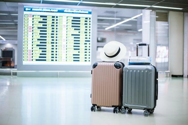 Le sac de voyage avec l'arrière est l'horaire du temps de voyage dans le terminal passagers de l'aéroport.