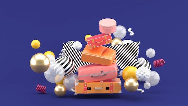Le sac de voyage se chevauche parmi les boules colorées sur le violet. rendu 3d.
