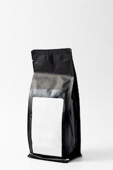 Sachet de café en plastique noir isolé sur fond blanc.