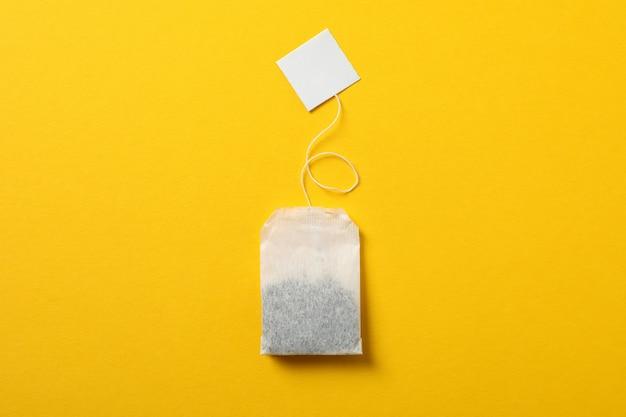 Sachet de thé avec étiquette sur jaune, espace pour le texte