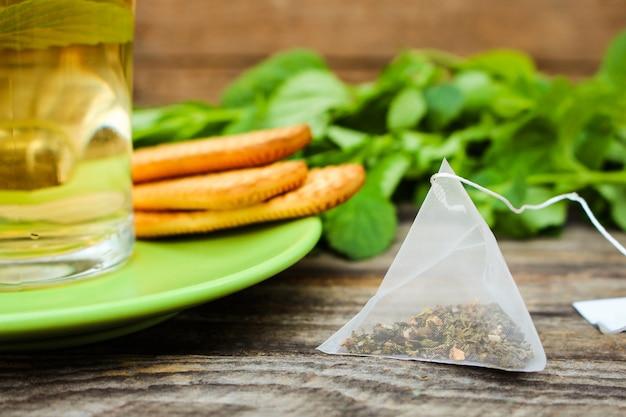 Sachet de thé sur fond de menthe, biscuit et tasse de thé