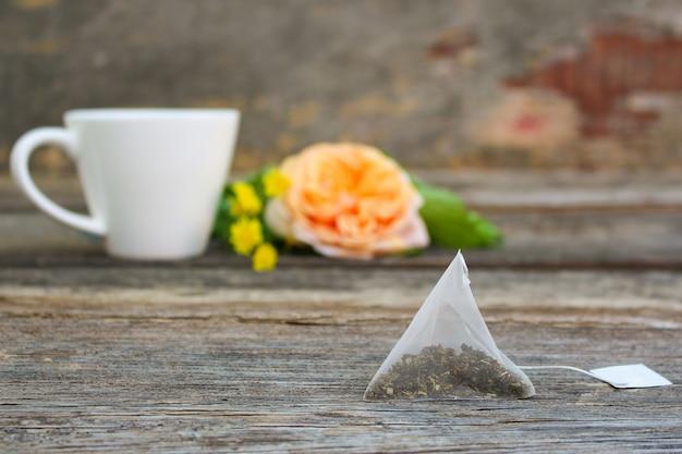 Sachet de thé sur fond de rose et et tasse de thé.