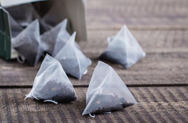 Sachet de thé en forme de pyramide sur fond de table en bois.