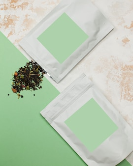Sachets en aluminium avec du thé vert avec étiquette verte pour le texte de la mise en page de votre logo