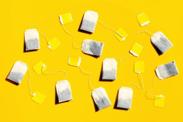 Sachets de thé sur fond jaune.