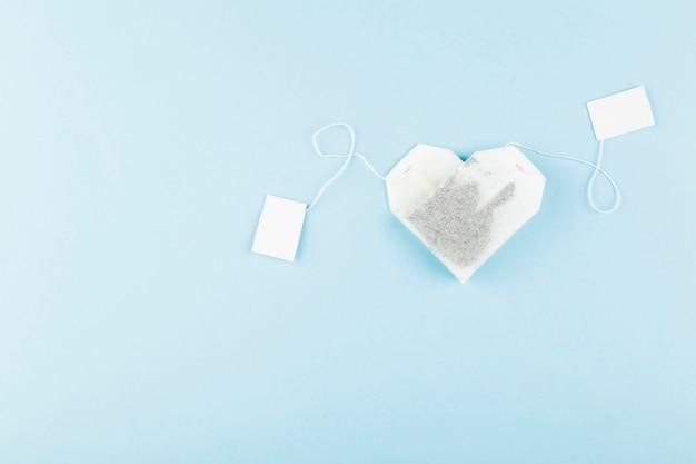 Sachets de thé en forme de coeur sur bleu. vue de dessus, surface