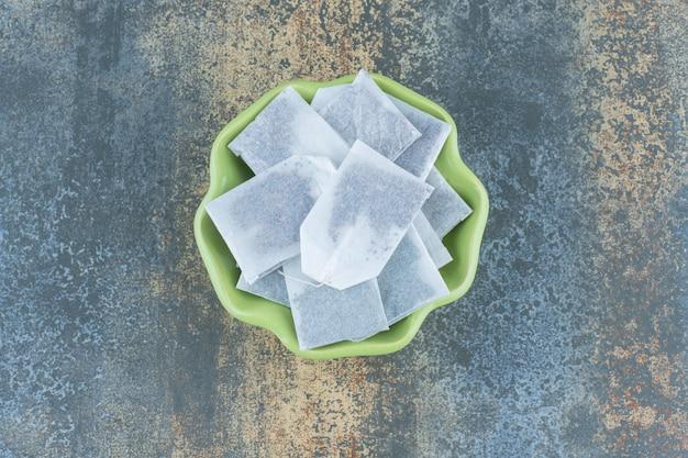 Sachets de thé noirs dans un bol vert sur marbre.