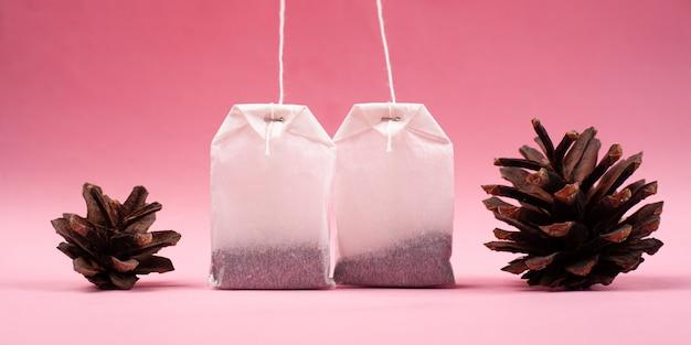 Sachets de thé en papier blanc avec des pommes de pin sur un gros plan de fond rose.